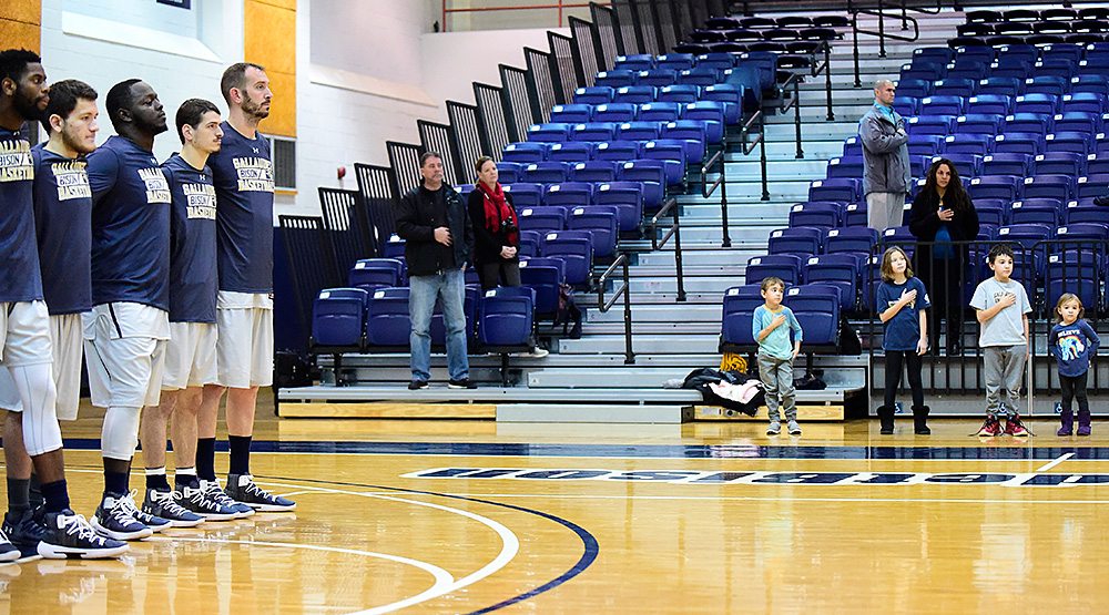 Steve Valencia-Biskupiak, on the far end, stands for the Star-Spangled Banner while his four children stand on the sideline as well. (Gallaudet athletics photo)