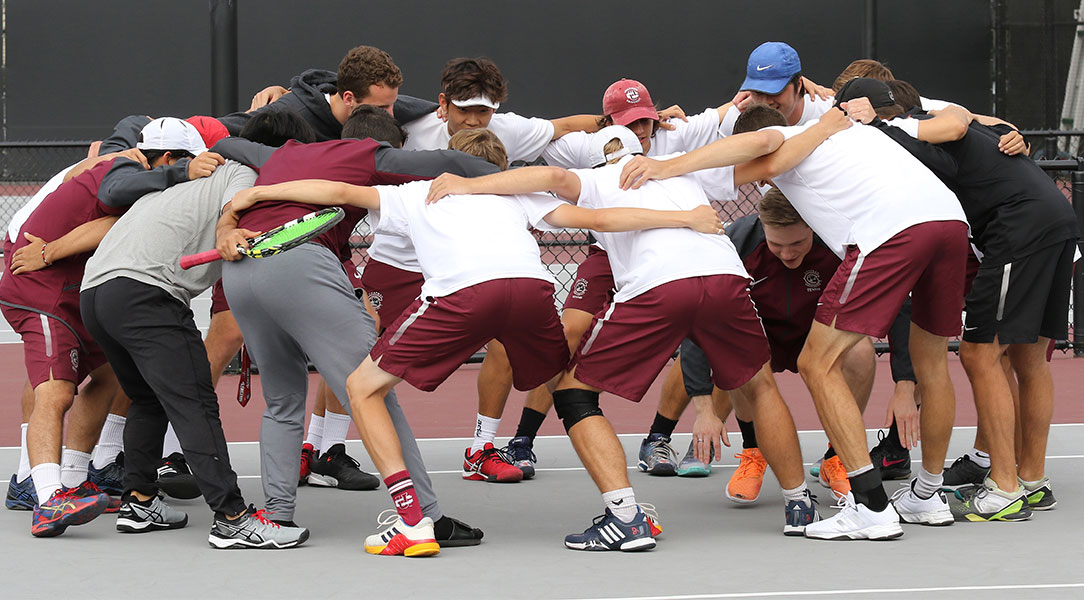 The men's tennis team huddles.