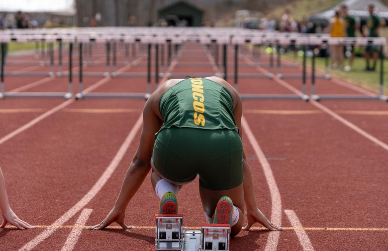 A SUNY Delhi hurdler positioned to begin a race.