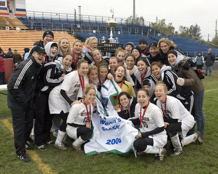 Team photo with championship banner at Queen's Richardson Stadium