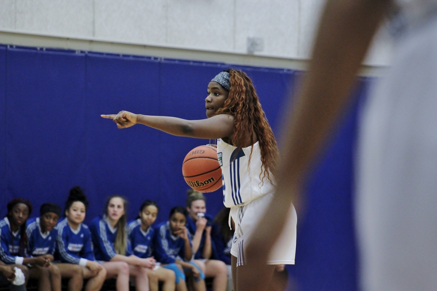 Female basketball player dribbling and pointing