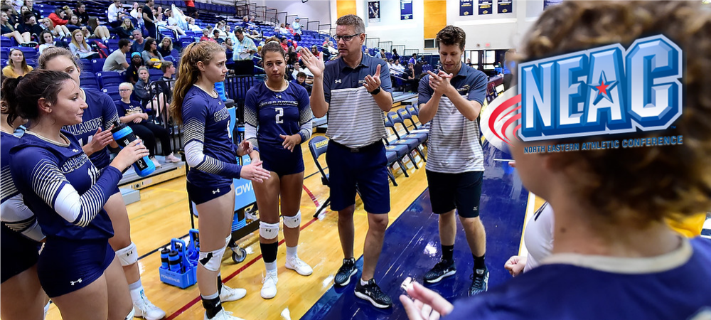 Gallaudet women's volleyball team huddles up during a timeout and go over strategy. People are clapping. A NEAC logo is in the upper right hand corner.