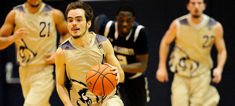 Gallaudet men's basketball player Trace Martin dribbles up the court. The orange basketball is in his left hand. GU is wearing special gold jerseys for the game.